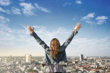 Dame mit gestreckten Armen auf einem Dach