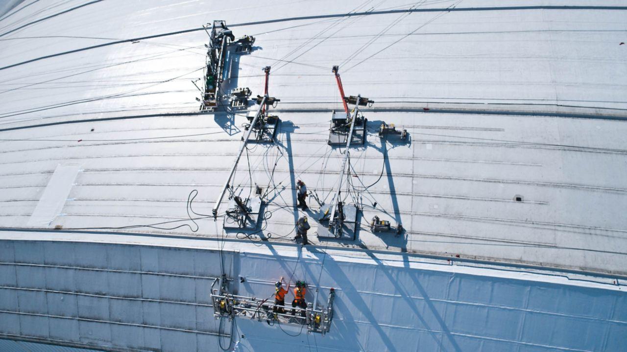 Worker reroofing Roger Center's roof