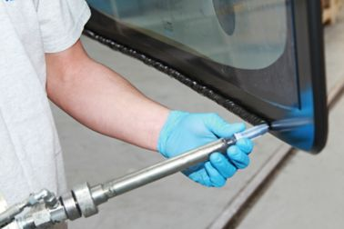 Applying adhesive to a train window with a pump system