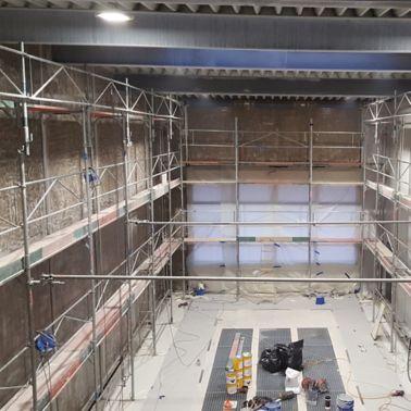 Nach Einrüstung der gesamten Wandfläche konnte mit der Sanierung der fehlerhaften Betondeckung der Fertigteile begonnen werden