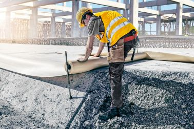 Bauarbeiter dichtet ein Bauwerk  ab