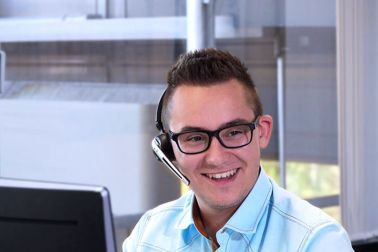 gut gelaunter Mitarbeiter am Telefon mit Headset