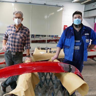 Geschäftsführer und Mitarbeiter bei der Reparatur einer Stoßstange