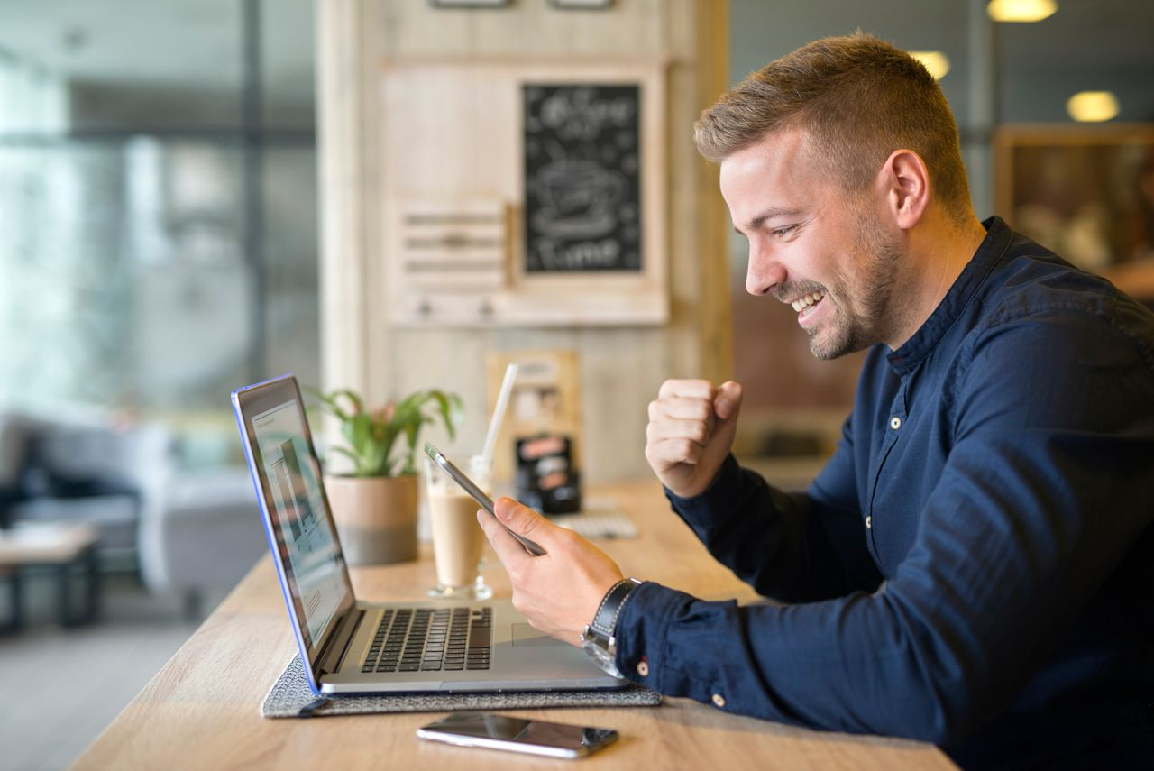 Happy freelancer with tablet and laptop computer in coffee shop.