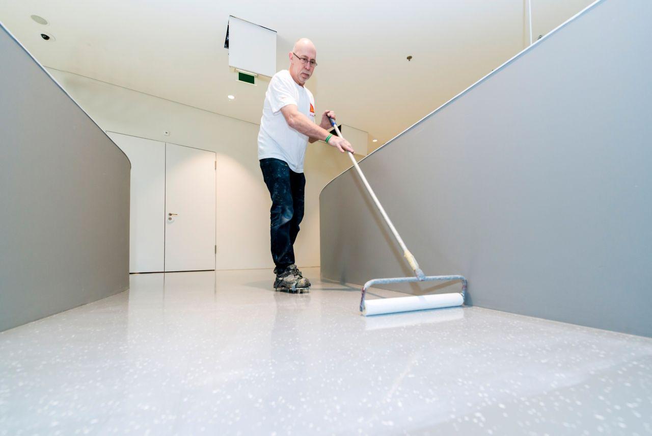 Mies viiimeistelee lattiapinnoitteen asennusta pintalakalla