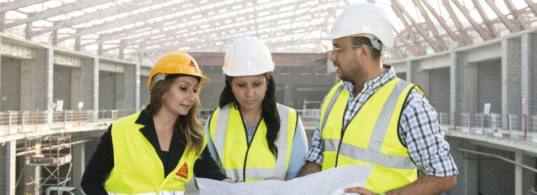 Architects and engineers reviewing plans on a construction site