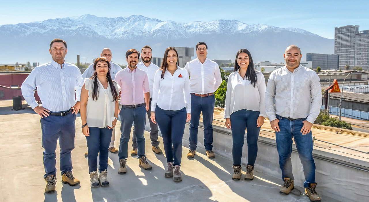 A group of people standing on top of a roof with mountains behind them