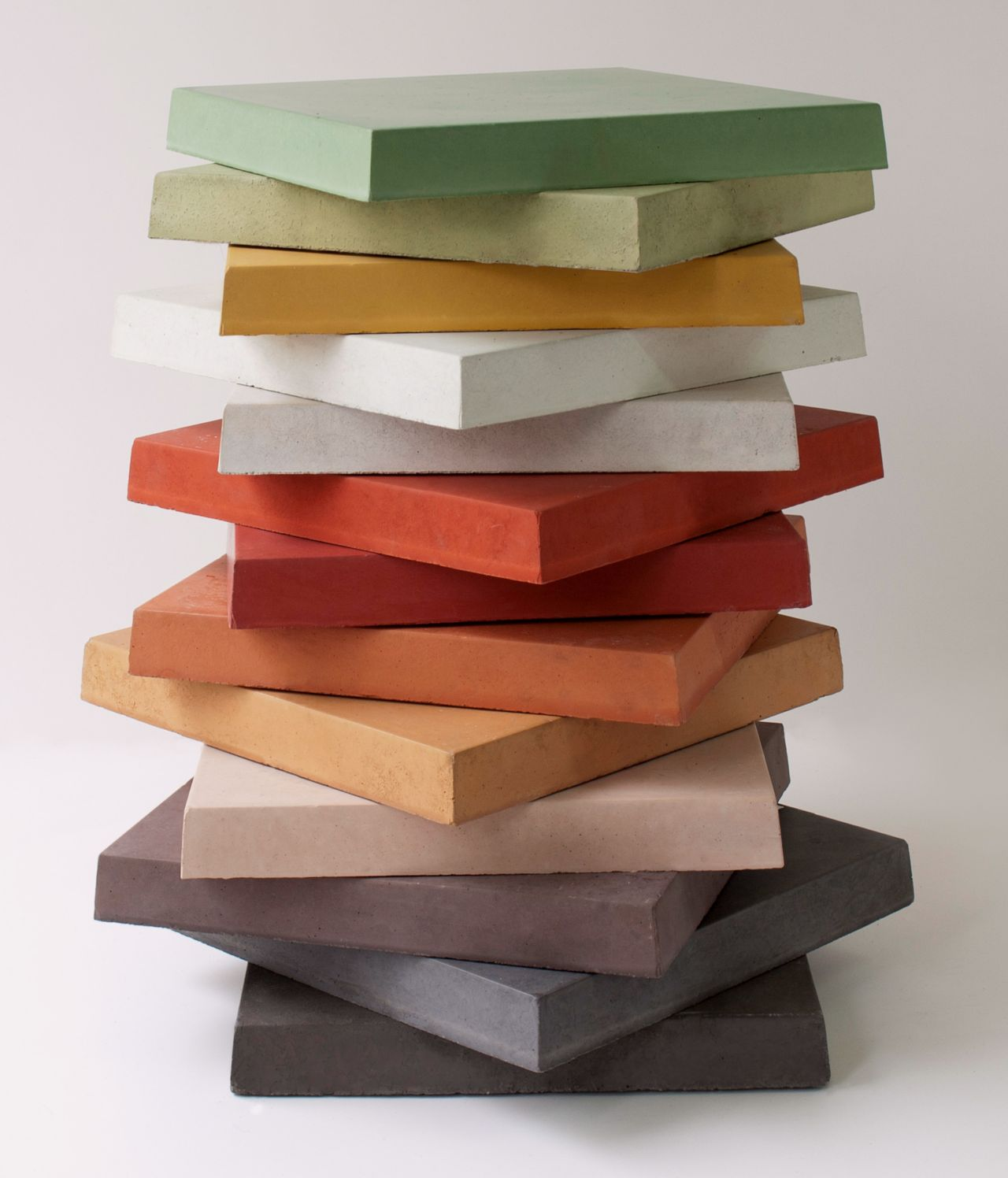 Colorful stack of concrete samples with Sika color concrete admixture in green, yellow, white, red, orange, peach, grey, charcoal and black