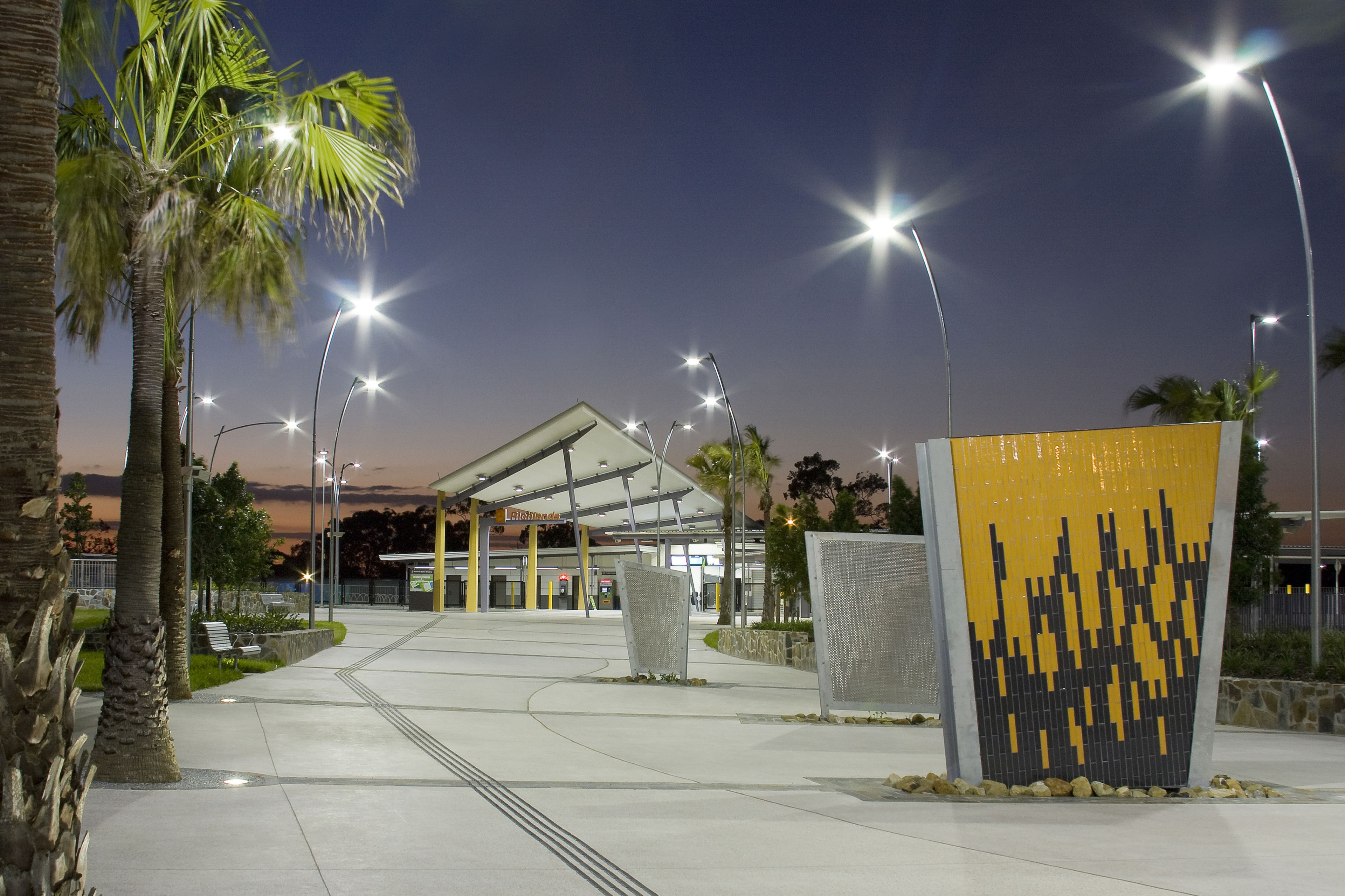 Smooth finished concrete sidewalk at transport station in Brisbane, Australia with guides for blind, palm trees and yellow tiled sculpture