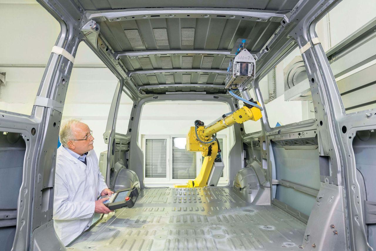 Sika engineer applying SikaDamp AutoPad vibration product via an Automatic robot