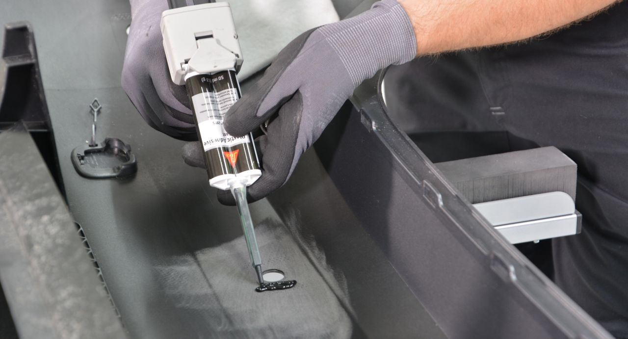 Travail de réparation en plastique en cours d'exécution sur un pare-chocs de voiture