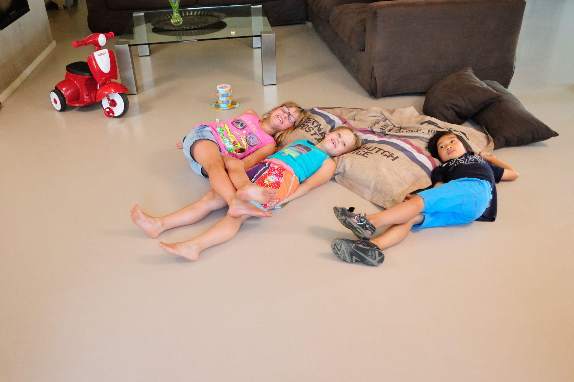 Sika ComfortFloor® beige grey floor with kids laying in living room