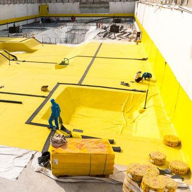 Construction workers applying a below-grade waterproofing membrane