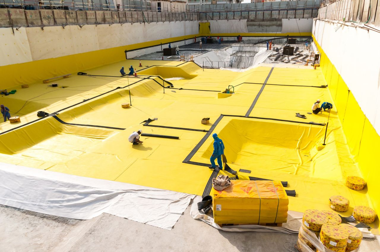 Construction workers applying a below-grade waterproofing membrane