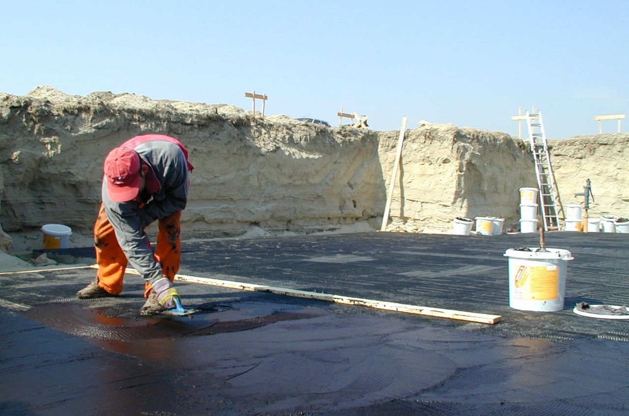 Man applying bituminous membrane on a building basement