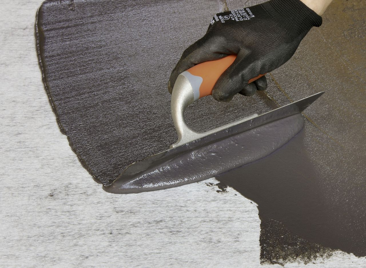 Application of cold-applied bitumen membrane with a hand trowel