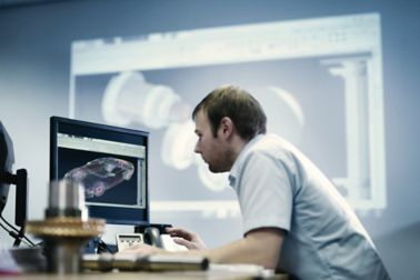 Man in front of a CAD computer drawing a drawing a car part
