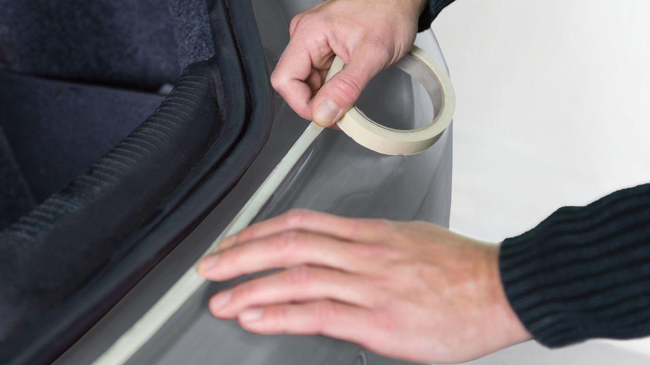 Mens die plakband toepast op een auto