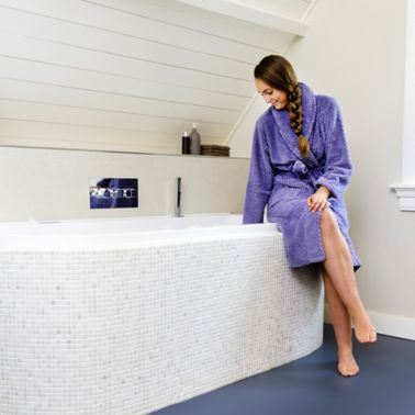 Sika ComfortFloor® blue floor in modern bathroom with bath tub and lady in robe