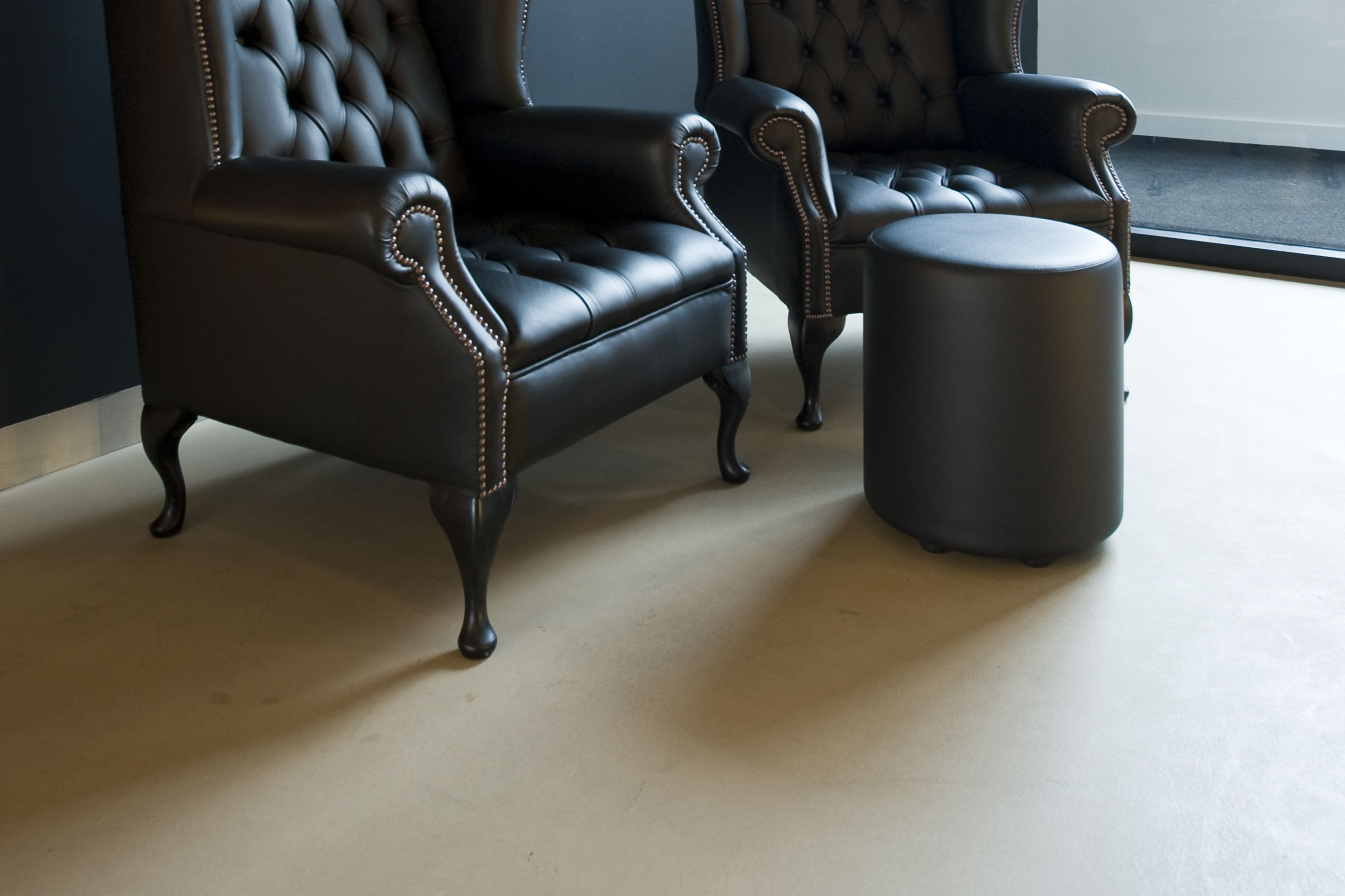 Sika ComfortFloor® beige floor with black wall and armchairs