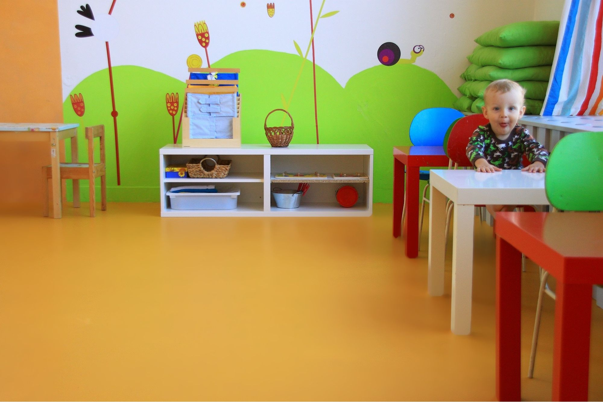 Sika ComfortFloor® orange floor in daycare with baby sitting on chair