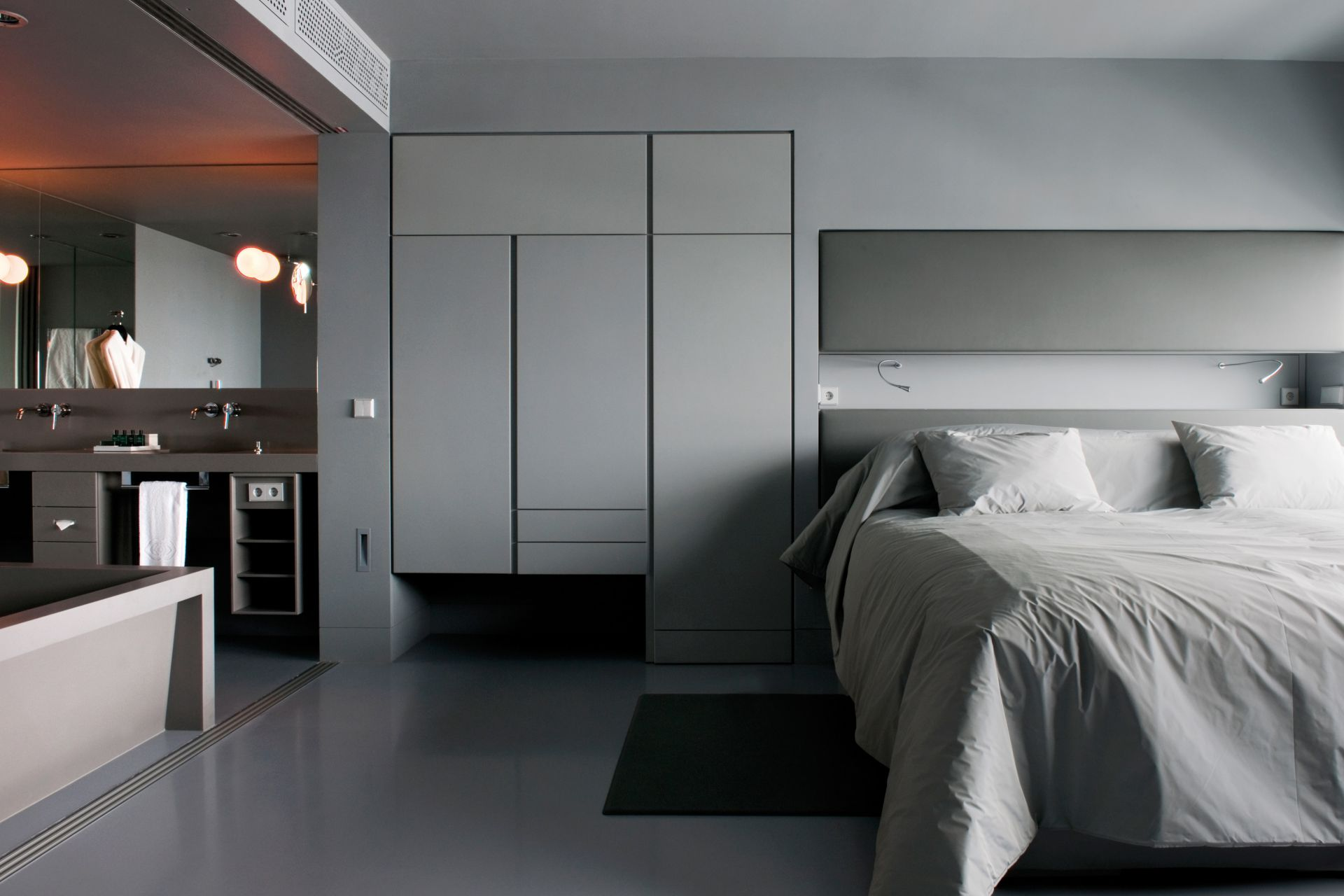 Sika ComfortFloor® grey floor in modern hotel room with bed and bathroom