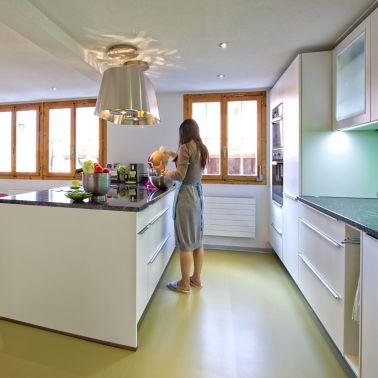 Sika ComfortFloor® green floor in kitchen with woman preparing food