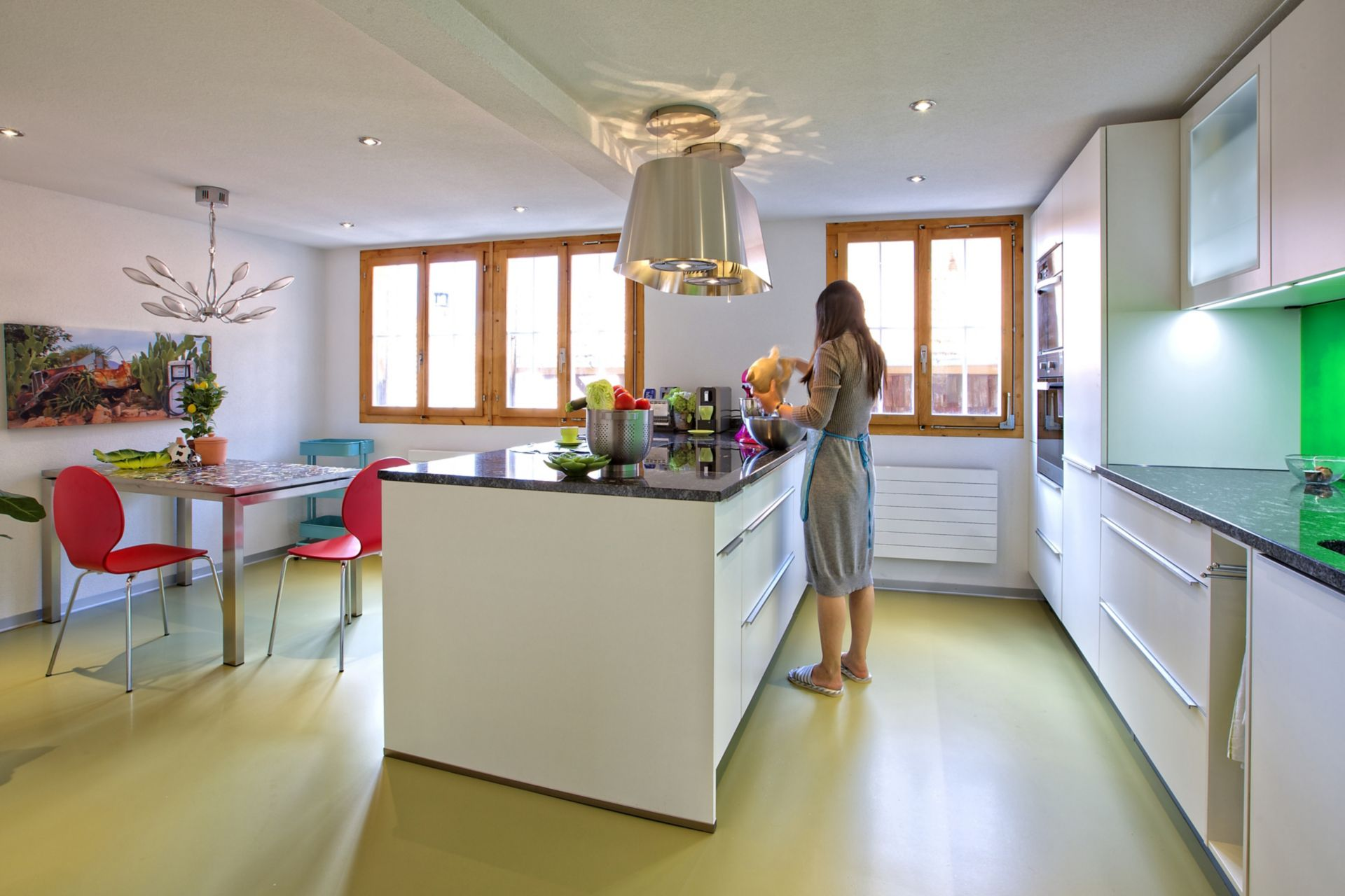 Sika ComfortFloor® green floor in kitchen with woman preparing food