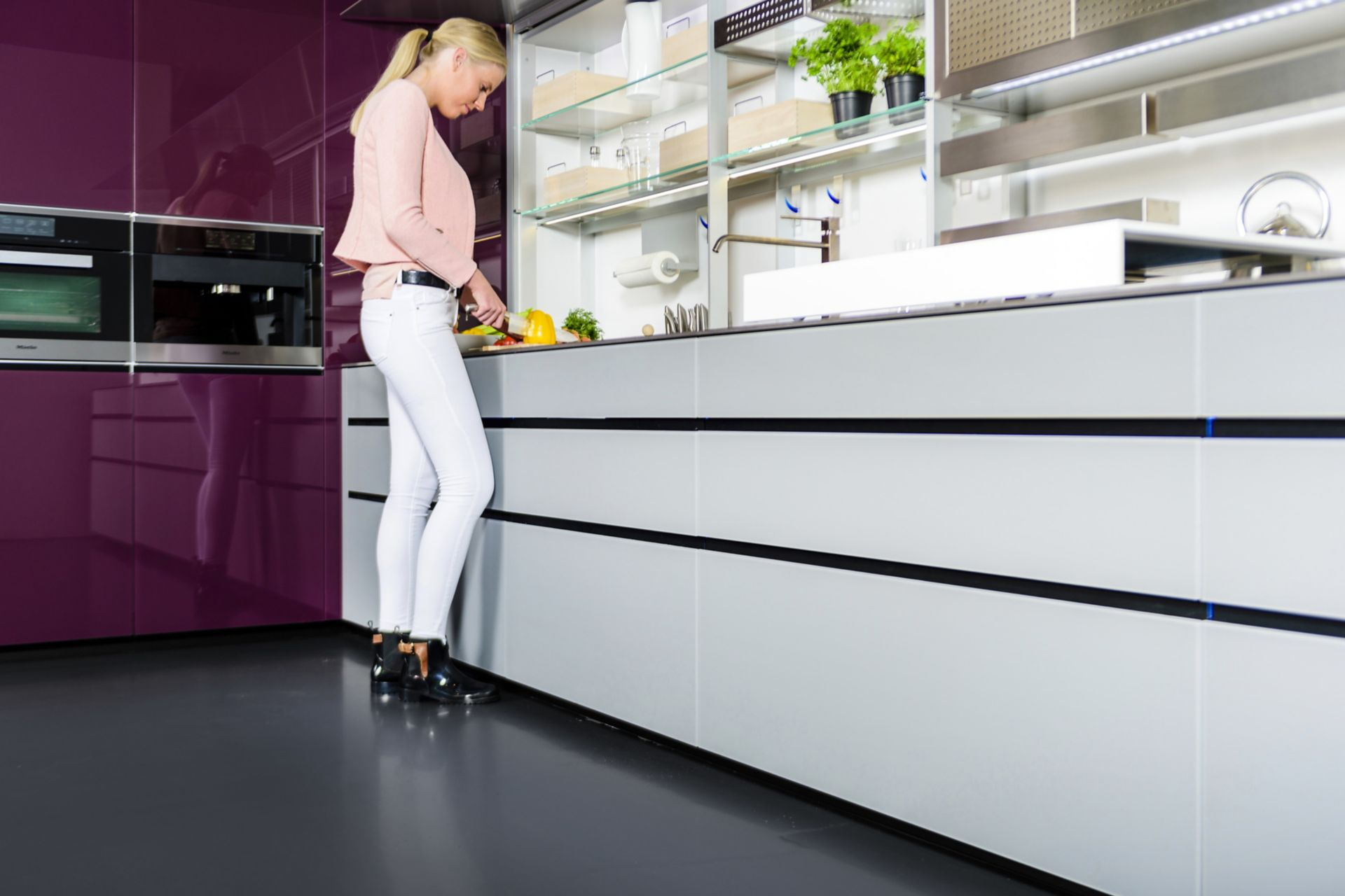Sika ComfortFloor® dark grey floor in kitchen with woman cutting vegetables