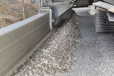 Machine extruding concrete on construction site with concrete fibers