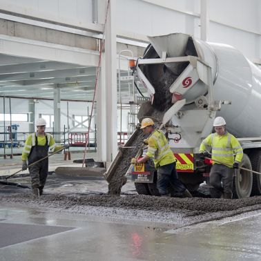 Workers pouring concrete from truck for concrete slab flooring with fibers