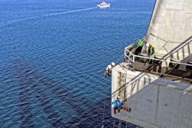 Man repairing a concrete bridge, hanging over the sea