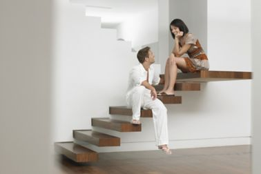 Couple sit on stairs in home with clean wall coating and wood floor