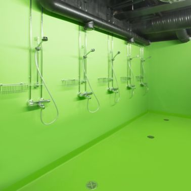 Decorative green bathroom shower floor at Kokkola campus hall school in Finland with Sika ComfortFloor system
