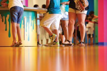 人们站在装饰橙色地板与西卡ComfortFloor系统