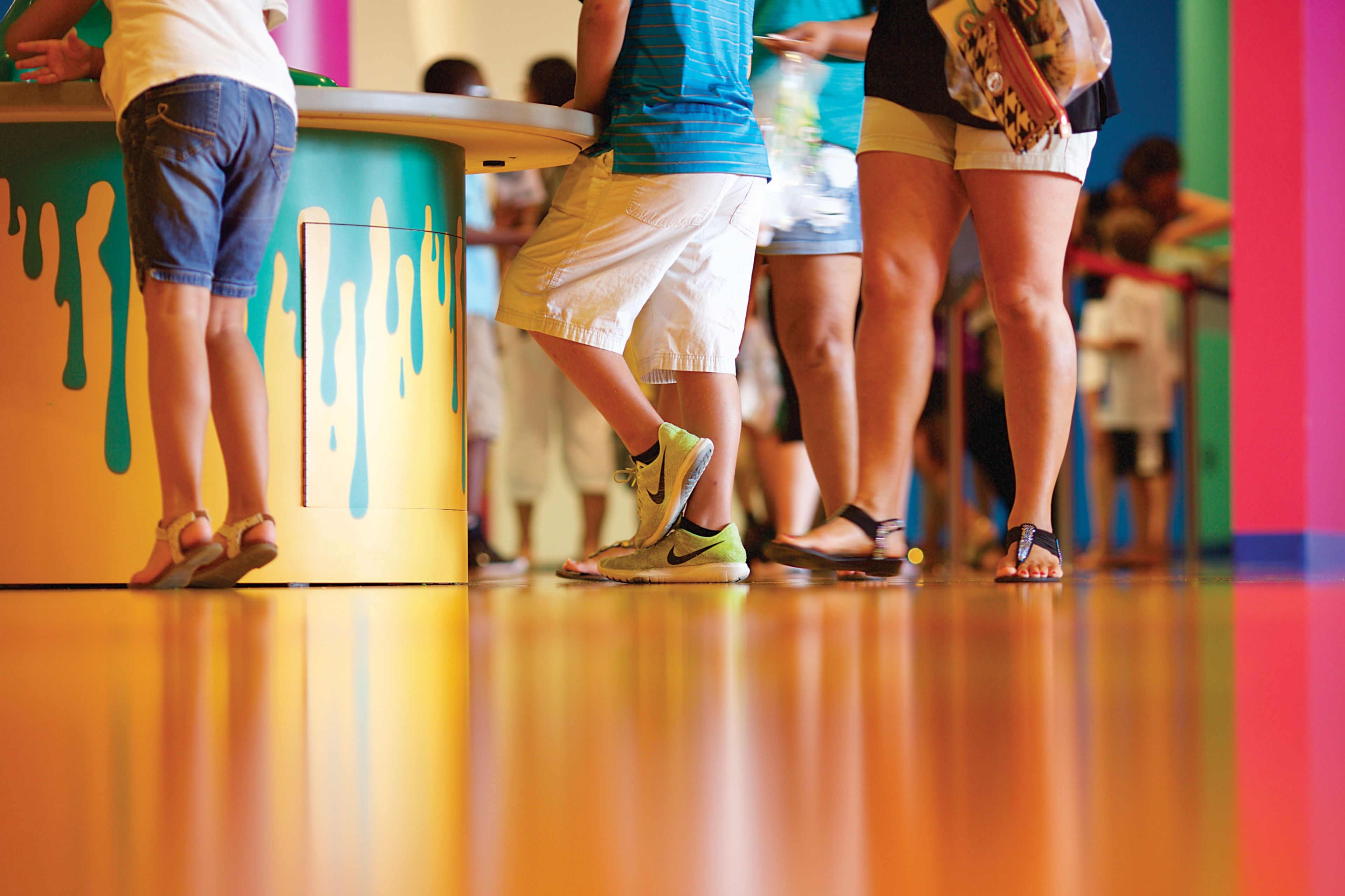 People standing on decorative orange floor made with Sika ComfortFloor system
