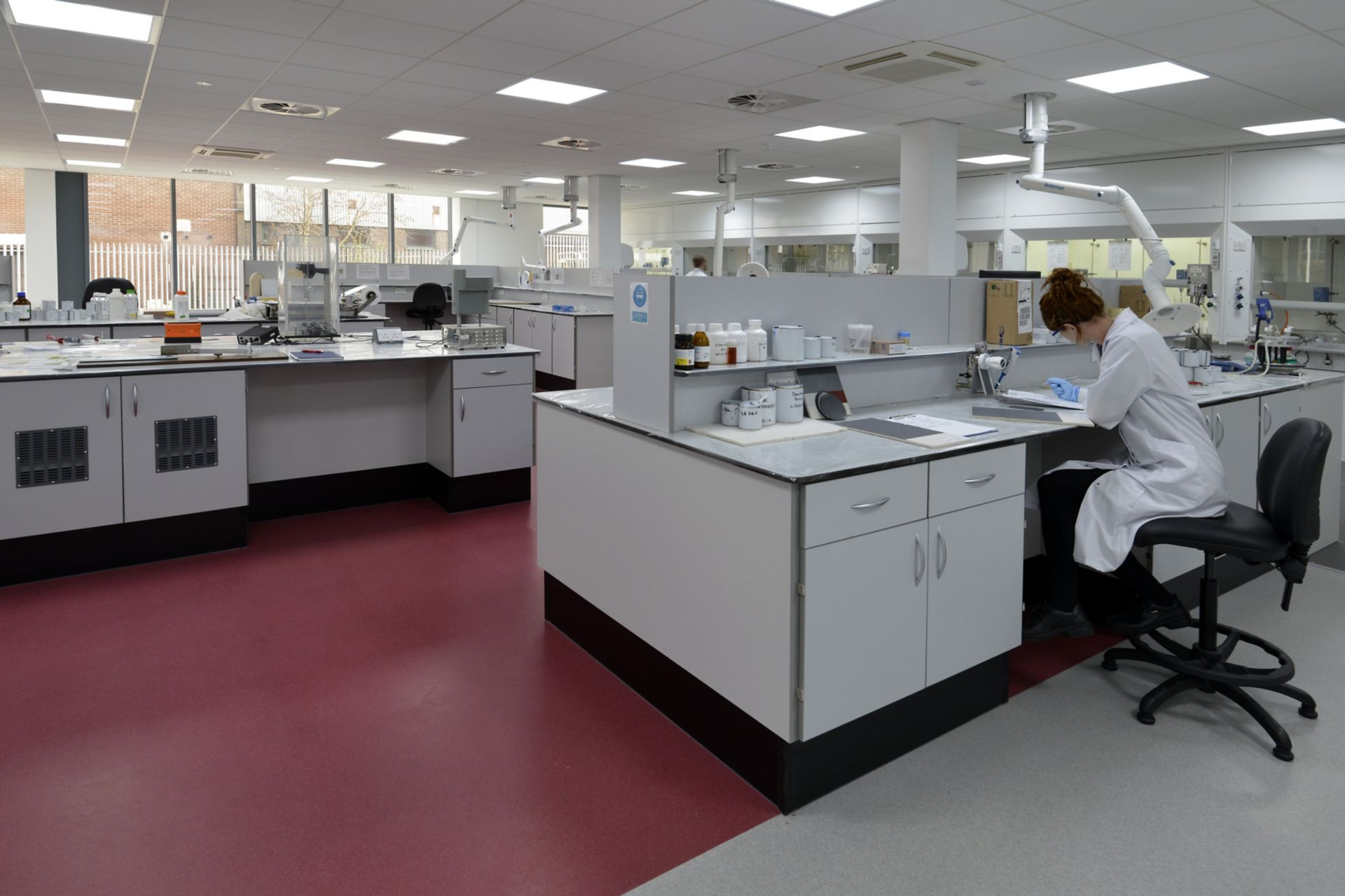 Clean red and white decorative laboratory interior floor with female research technician at work