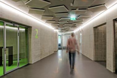 Man walking in corridor office building on grey Sika ComfortFloor concrete walls at Limmat building in Zurich