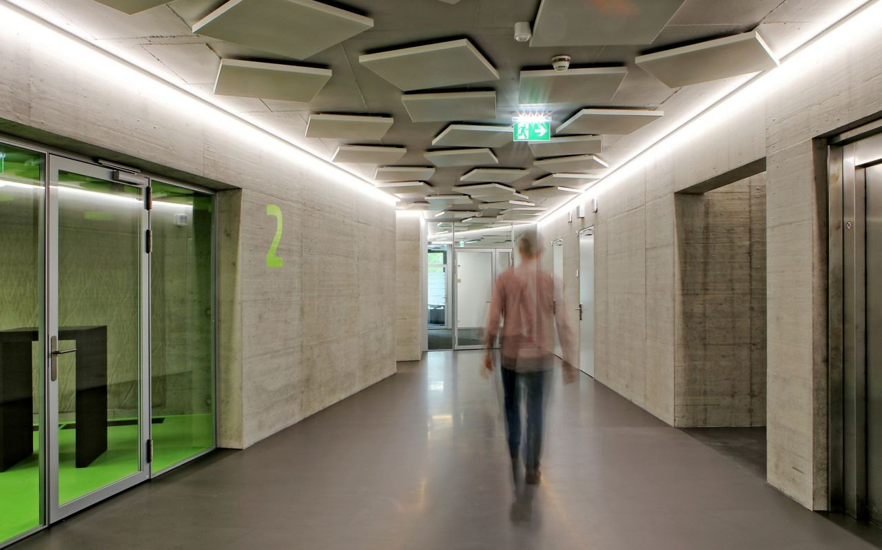 Man walking in corridor office building on grey Sika ComfortFloor concrete walls at Limmat building in Zurich