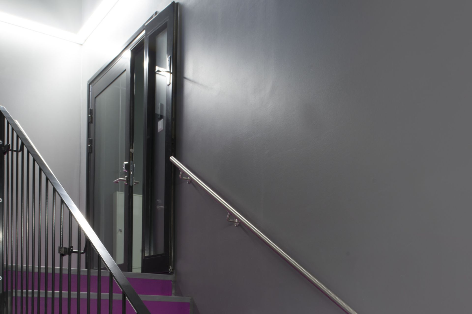 Decorative purple fushia stair floor grey walls at Kokkola campus hall school in Finland with Sika ComfortFloor system
