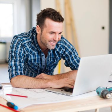 Smiling DIY construction worker man working with laptop