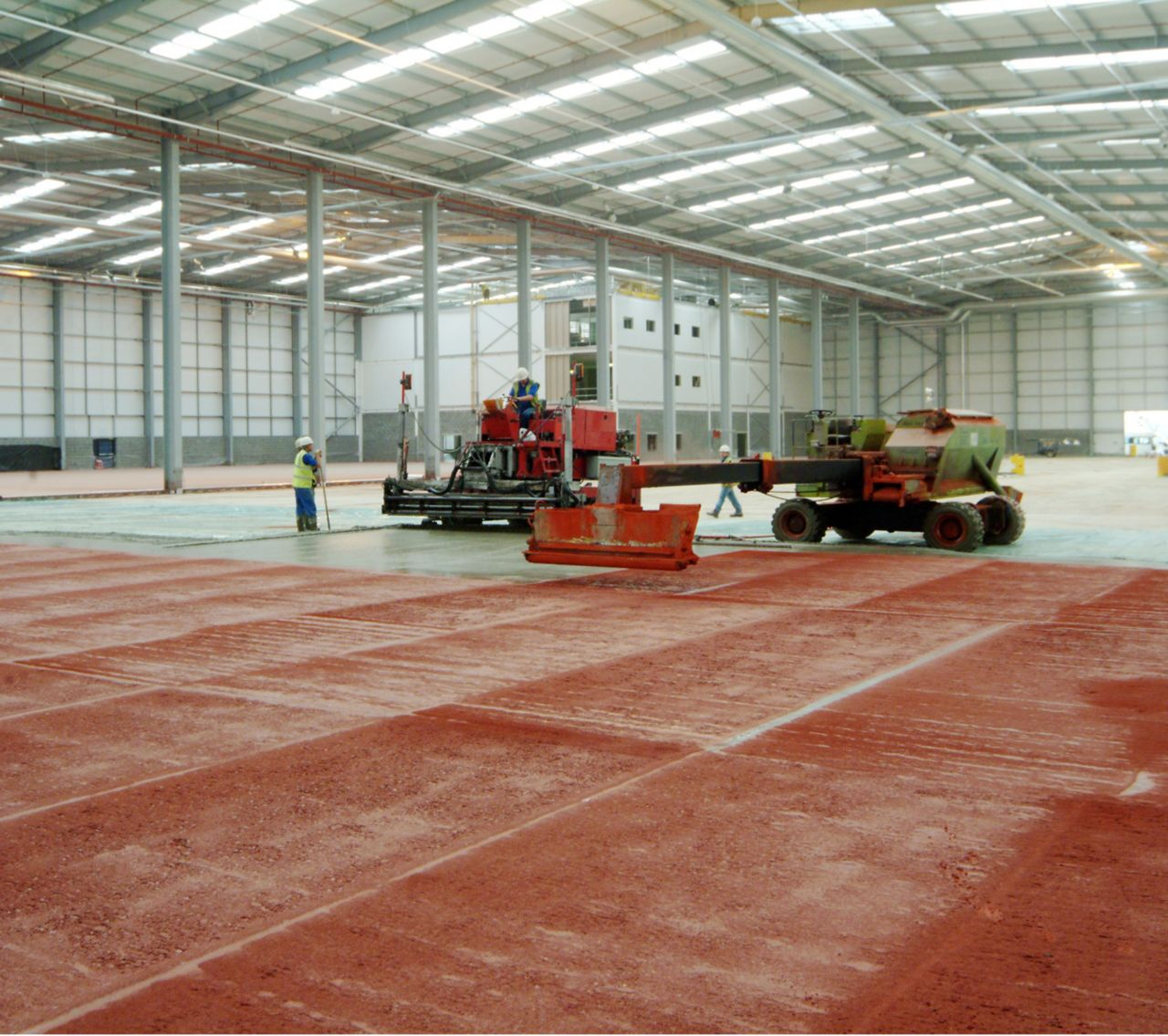 Dry shake hardeners broadcasted directly onto fresh concrete floor in warehouse
