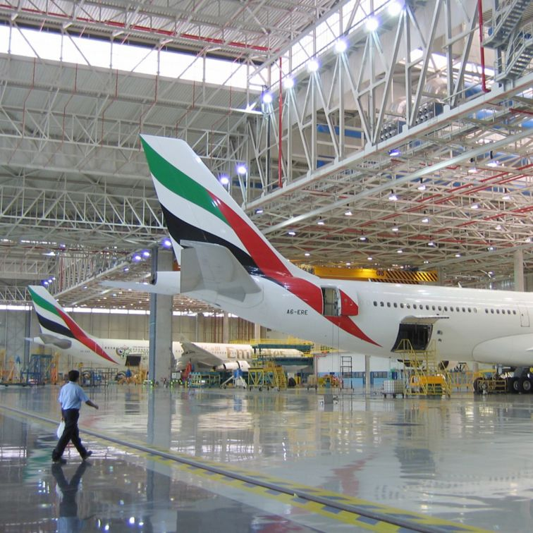Dubai International Airport Emirates hangar with planes and man walking