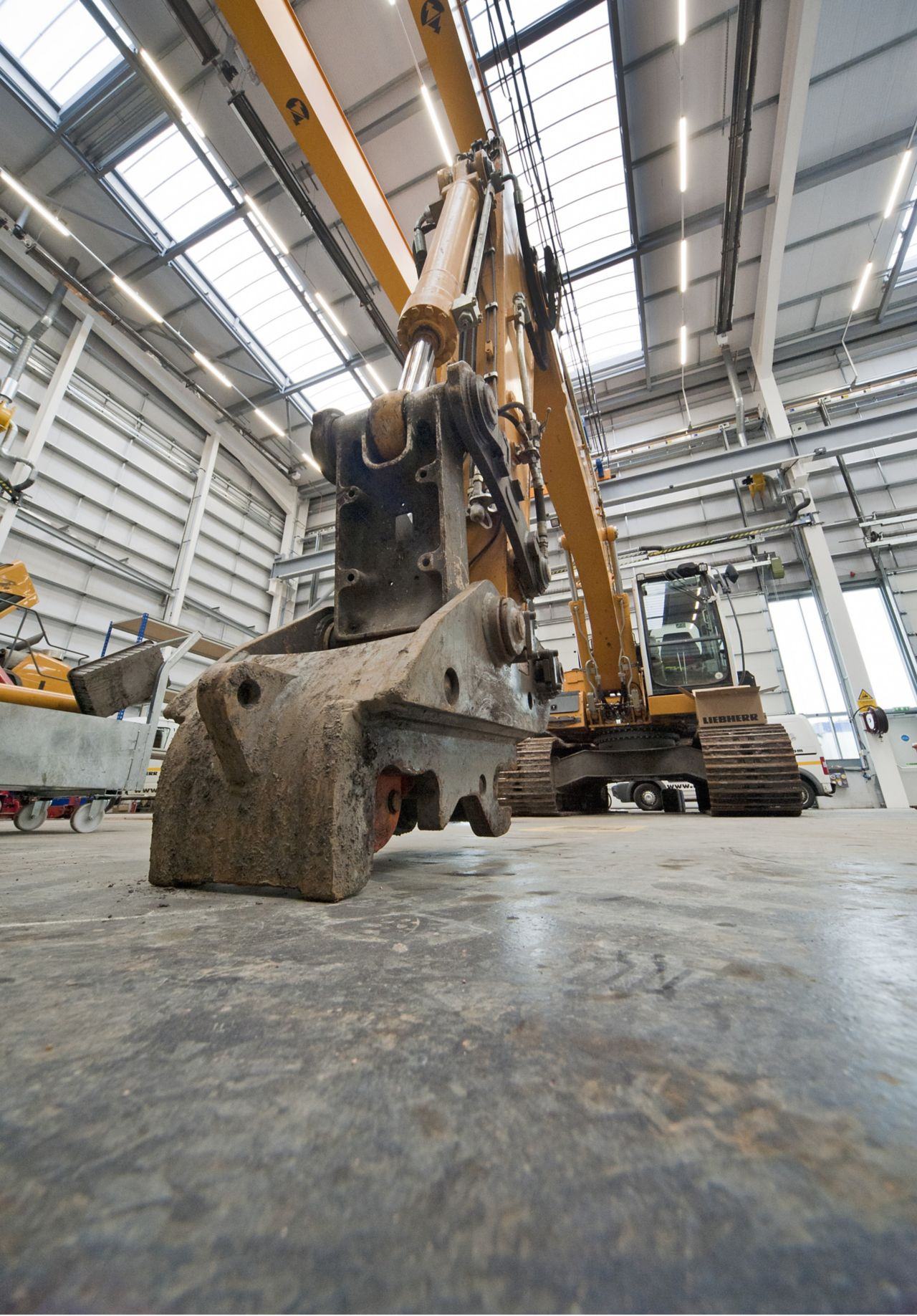 Excavator on a concrete floor with dry shake aggregate floor hardeners