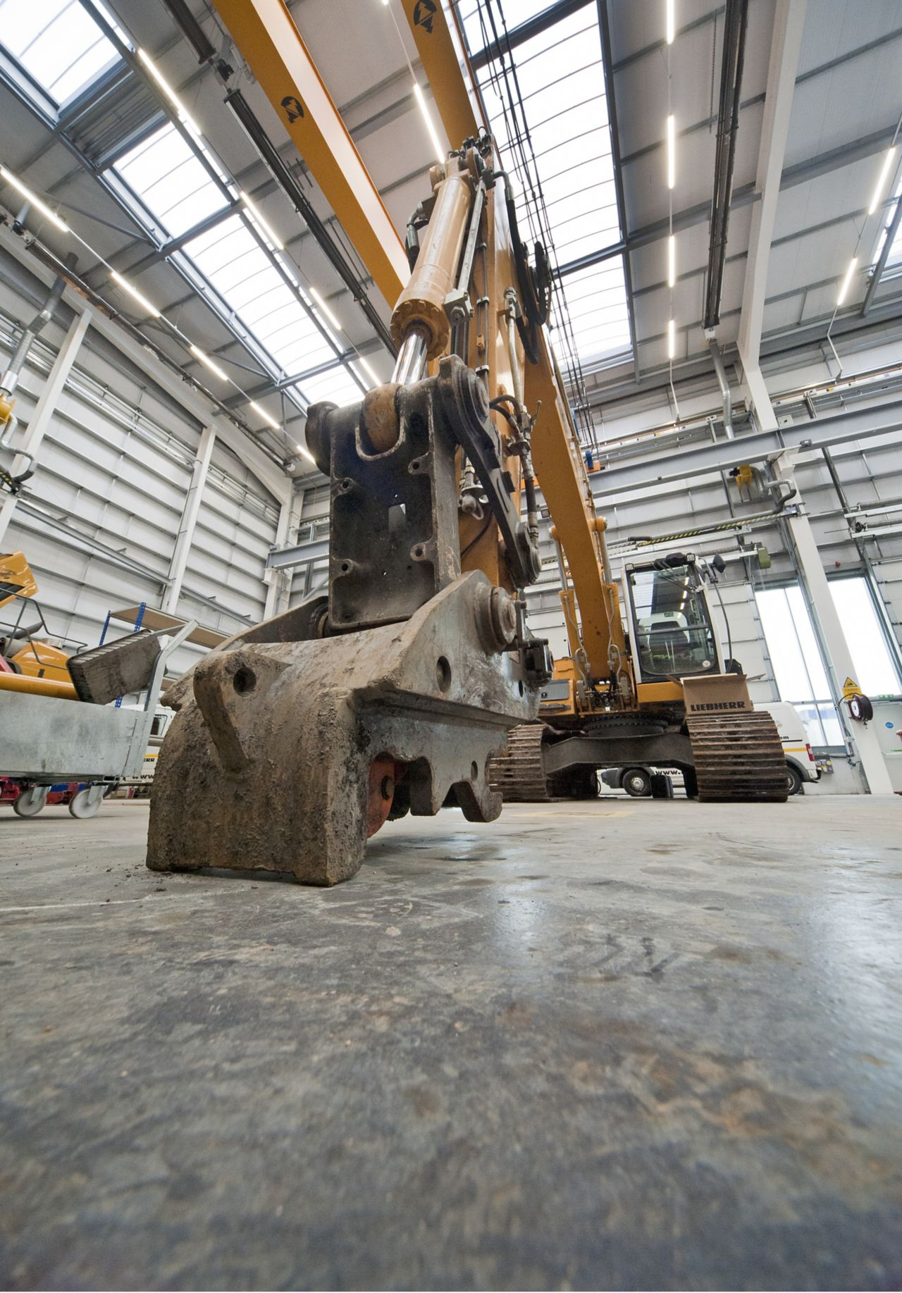 Excavator on a concrete floor with dry shake aggregate floor hardeners