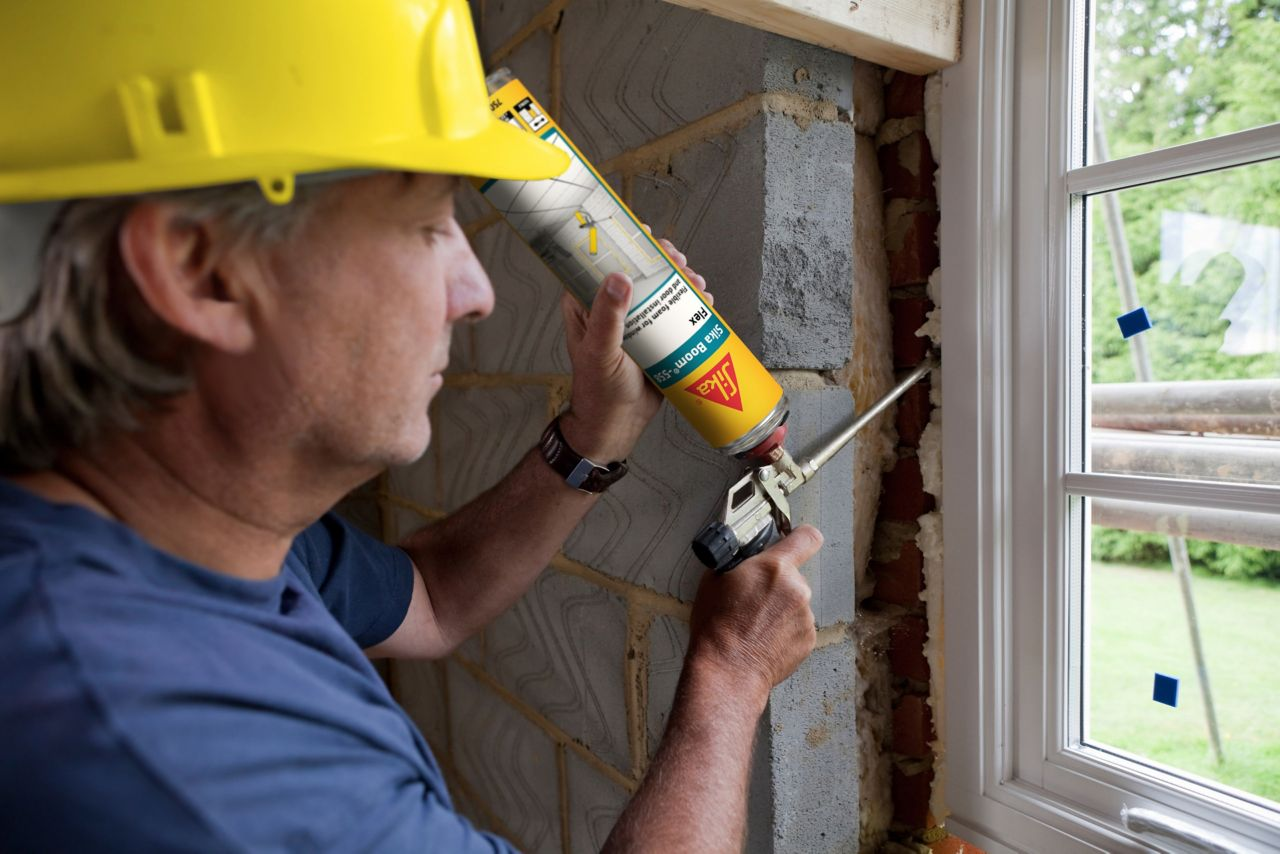 Man applying Sika Boom expansion foam between a window and a wall