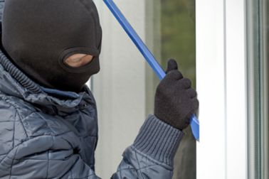 Man trying to break in a house through a burglary proof bonded window