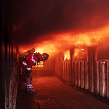Fireman in front of house on fire