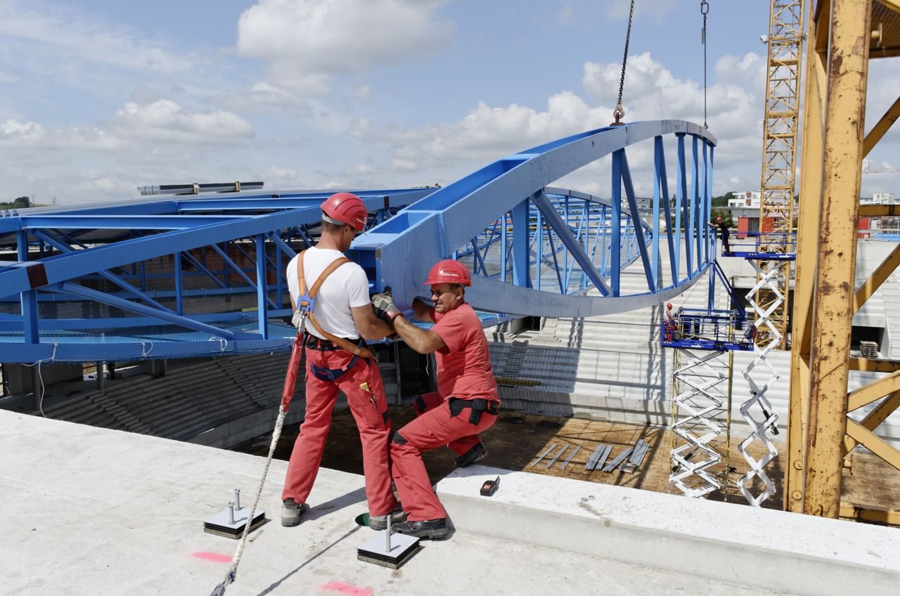 Men installing steel truss beam with Sika intumescent fire resistant coating