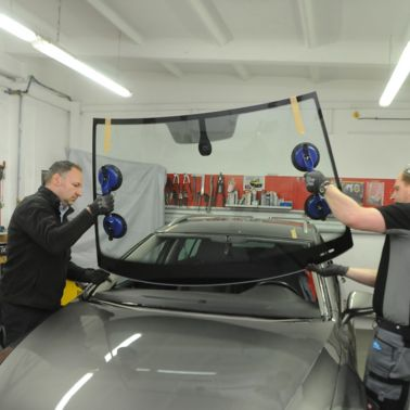 Two fitter placing windshield into frame of a car